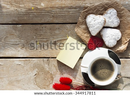 Heart shaped cookies (powdered sugar), cup of coffee, decoration (red flowers, heart toy) on old wooden table. sunny morning.  Christmas breakfast or Valentine's Day Breakfast. Toned image