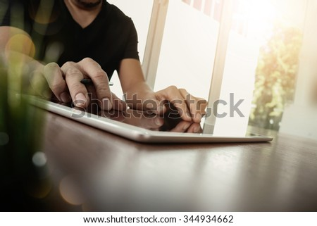 businessman working with digital tablet computer on wooden desk with green plant foreground as concept #344934662