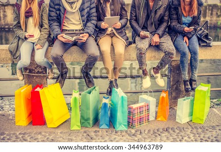 Group of friends sitting outdoors with shopping bags - Several people holding smartphones and tablets - Concepts about lifestyle,shopping,technology and friendship #344963789