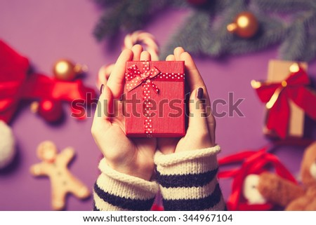 Female hands are holding a christmas gift on violet background #344967104