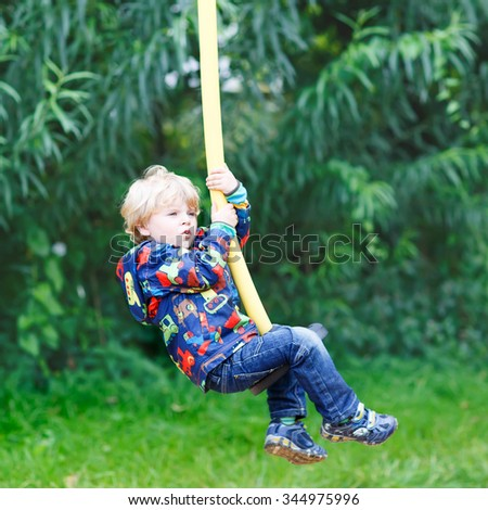 Little smiling boy of three years having fun on swing on sunny summer day, outdoors. Active sports with kids. #344975996