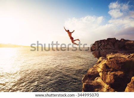Cliff Jumping into the Ocean at Sunset, Summer Fun Lifestyle Royalty-Free Stock Photo #344995070