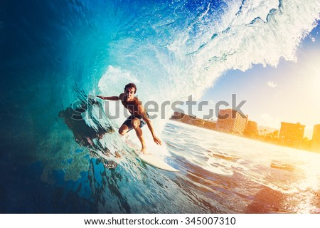 Surfer on Blue Ocean Wave Getting Barreled at Sunrise Royalty-Free Stock Photo #345007310