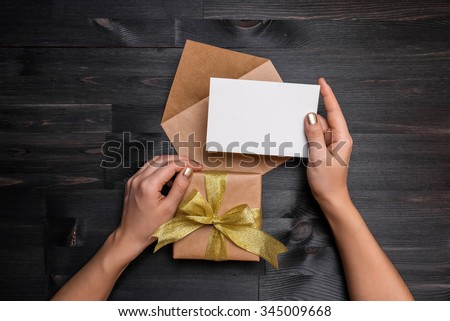 Female hands holding gift card and gift box over the black wooden table Royalty-Free Stock Photo #345009668
