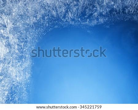 Frosty patterns on the edge of a frozen window. #345221759