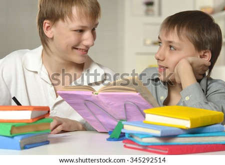 Two brothers doing homework at home at table #345292514