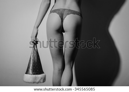 Posing back to camera beautiful sexy young lady in perfect shape wearing lace lingerie and holding Santa Claus hat. Black and white photography