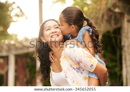 Woman giving piggyback ride to her daughter