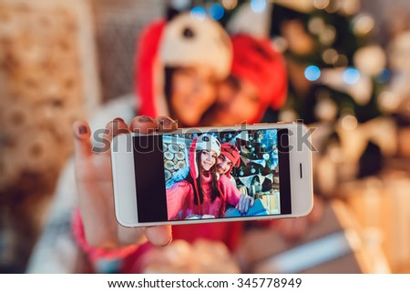 Loving couple dressed in funny hats doing selfie. Christmas decorations.