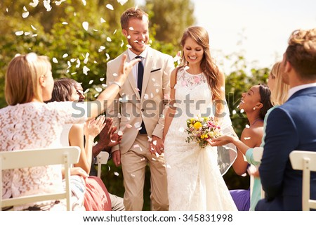 Guests Throwing Confetti Over Bride And Groom At Wedding Royalty-Free Stock Photo #345831998
