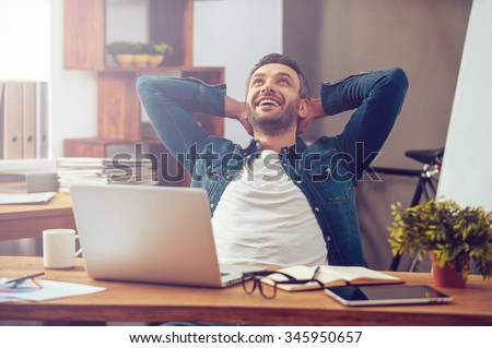 Satisfied with work done. Happy young man working on laptop while sitting at his working place in office Royalty-Free Stock Photo #345950657