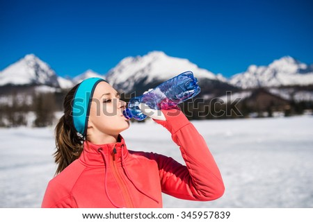 Young woman jogging outside in sunny winter mountains #345957839