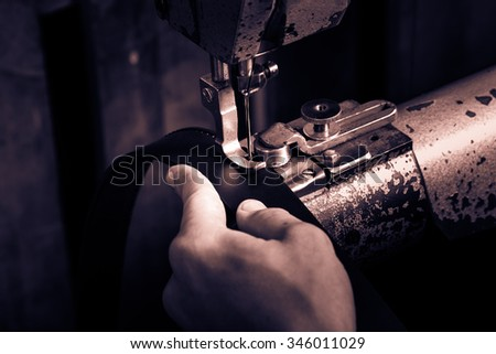 Sewing process of the leather belt. Man's hands behind sewing. Leather workshop. Black and white photography.