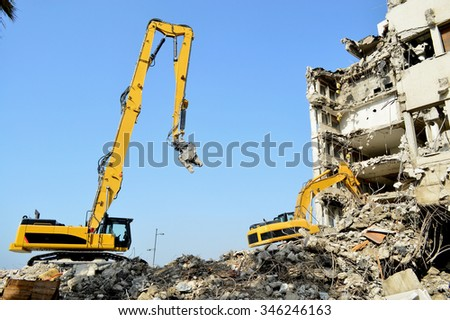 high reach demolition excavator tearing down a high building Royalty-Free Stock Photo #346246163