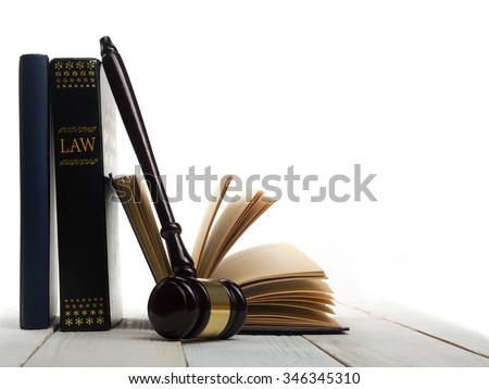 Law concept - Open law book with a wooden judges gavel on table in a courtroom or law enforcement office isolated on white background. Copy space for text #346345310