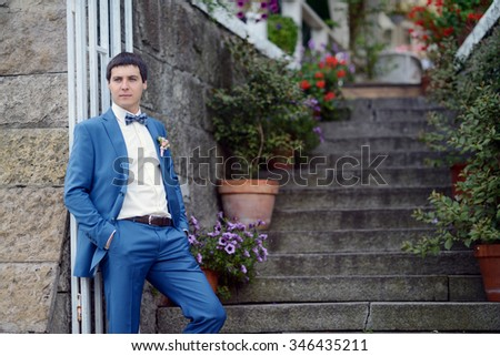 Handsome groom in suit on the nature. Male portrait in the park. Beautiful model boy in colorful wedding clothes. Man is posing. Handsome guy outdoors #346435211