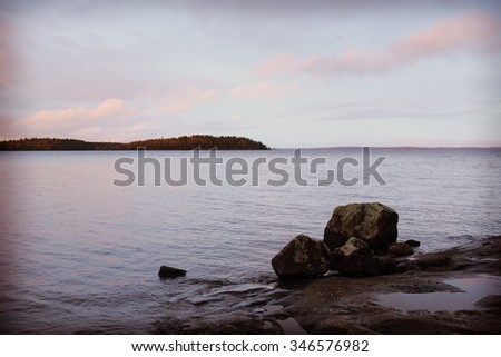 A beautiful scenery by the lake. Image taken on a cloudy day and some rocks are in the water where the focus point is. Image has a vintage effect applied. #346576982