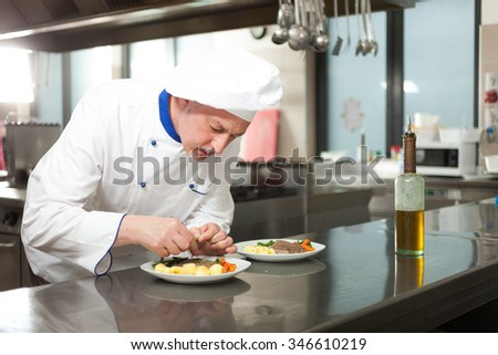 Male chef dressed in white uniform decorating a dish #346610219