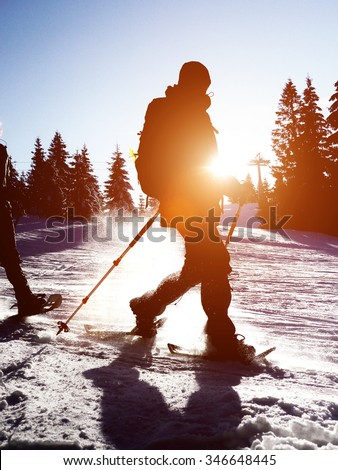 Cross country skier at sunrise or sunset moving through the snow with a sunburst over his shoulder #346648445