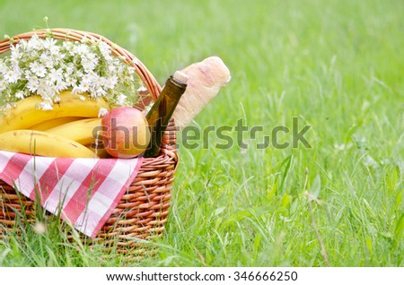 Picnic basket with apples bananas cheese and wine on green grass #346666250
