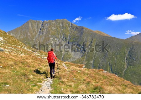 Backpacker woman departing on a sunny trail above the mountains #346782470