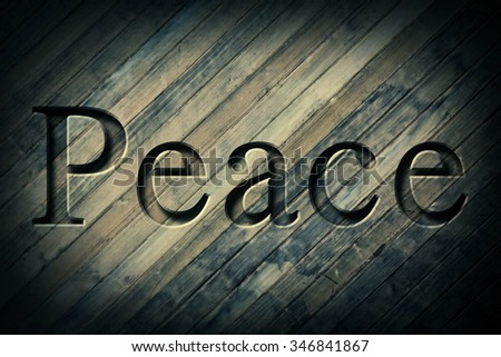 Engraving spelling the word Peace on textured old surface #346841867
