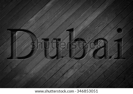 Engraving spelling the city Dubai on textured old surface #346853051