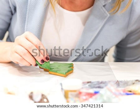 Girl painting christmas gingerbread in art studio with sweet icing #347421314