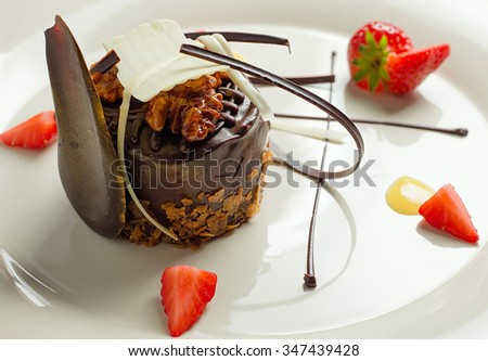 Beautiful dessert: chocolate cake with nuts on a plate close-up. horizontal #347439428