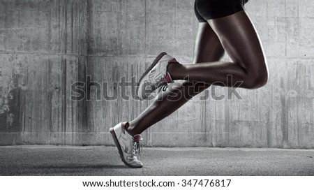 Sports background. Runner. Side view of a jogger legs on concrete wall #347476817