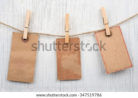 Labels on clothesline on retro wooden background and space for text #347519786