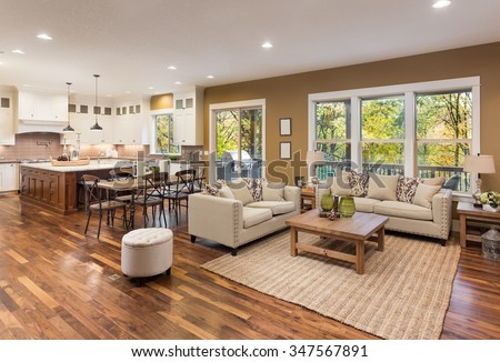 Beautiful living room interior with hardwood floors and view of kitchen in new luxury home Royalty-Free Stock Photo #347567891