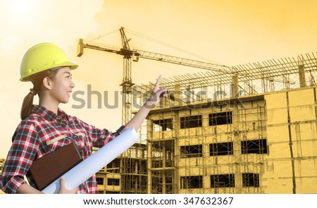 portrait women asia engineer working and holding blueprints at construction site #347632367