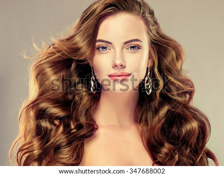 Beautiful girl with long wavy hair .  Brunette with curly hairstyle #347688002