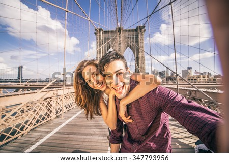 Beautiful couple taking selfie on Brooklyn Bridge, New York - Tourists having fun and photographing NY landmarks #347793956
