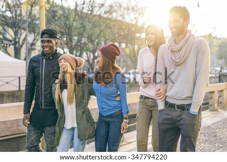 Group of multi-ethnic friends walking on the streets and smiling - Young people having fun outdoors #347794220