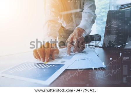 business documents on office table with smart phone and digital tablet and graph financial with social network diagram and man working in the background Royalty-Free Stock Photo #347798435