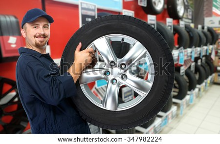 Smiling car mechanic with a tire over garage background. #347982224