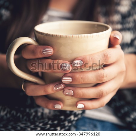 Girl's hands holding a cup of coffee. Fashion manicur