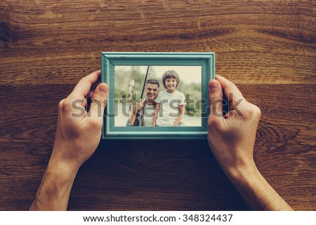My son is my life. Close-up top view of man holding photograph of himself and his son fishing over wooden desk