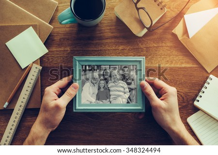 My family is my inspiration. Close-up top view of man holding photograph of his family over wooden desk with different chancellery stuff laying around