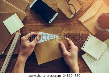 Opening envelope. Close-up top view of male hands opening envelope over wooden desk with different chancellery stuff laying on it Royalty-Free Stock Photo #348324530