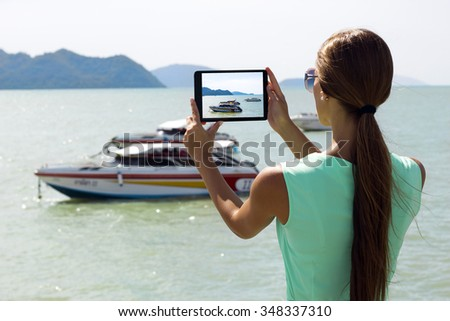Woman traveler photographing sea island view with digital tablet on pier of boat station. Phuket, Thailand