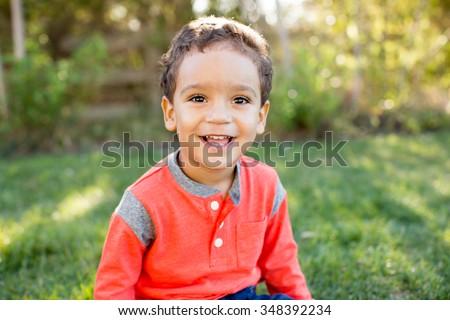 Cute little boy sitting in the grass outside