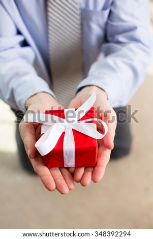 Man holding a red gift box with white ribbon #348392294