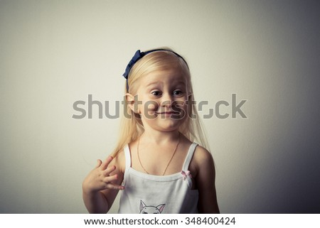 Adorable toddler girl looking strange in front of the camera. #348400424