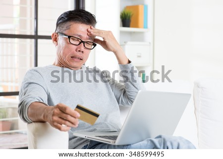 Portrait of 50s mature Asian man having problems while using computer internet doing online payment with credit card, sitting on sofa at home. #348599495