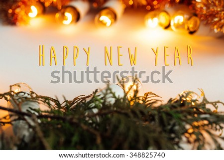 green branches and amazing christmas golden vintage garland lights on white background, happy new year text #348825740