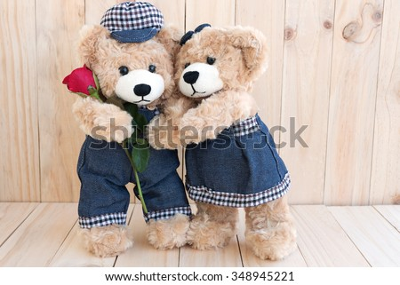couple teddy bears with red rose on wood background, love concept for valentines day, wedding and anniversary