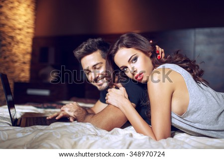 Young couple lying on bed with laptop, online shopping #348970724